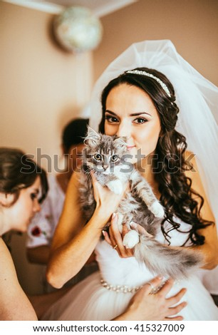 Bridal portrait. Woman preparing for her wedding and her cat - stock photo