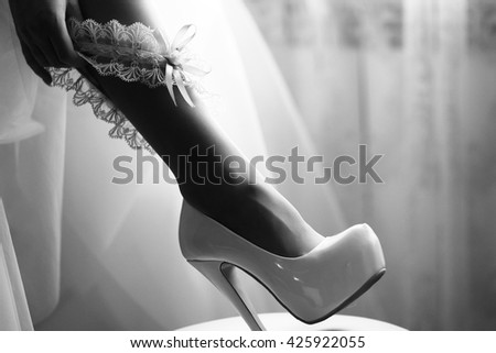 Bridal sexy leg in elegant high heel shoe with putting on beautiful ribbon wedding garter by female hand, black and white - stock photo