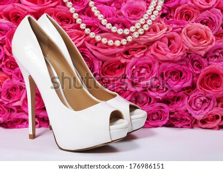 Bridal Shoes and Roses. White Heels over Hot Pink Flowers with Pearl Necklace.  Wedding - stock photo