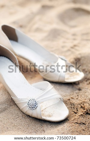 bridal shoes on left sands in a beach wedding party - stock photo