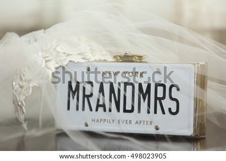 Bridal veil with Mr and Mrs placard surmounted with a gold model car with the words Happily Ever After below celebrating the marriage of two newlyweds