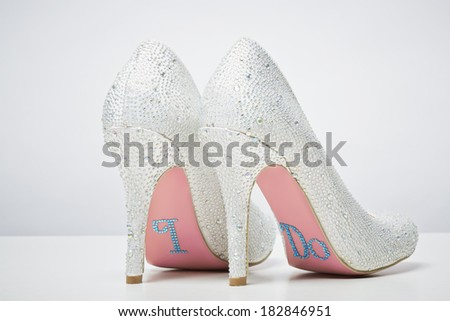 Bridal wedding shoes with I do message on sole isolated on white background. Marriage concept - stock photo