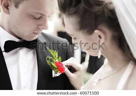 bride adjusting flower on groom's jacket - stock photo