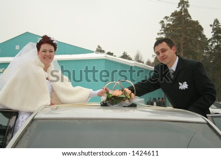 Bride and bridegroom are taken pictures beside car