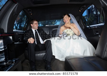Bride and bridegroom in a luxury wedding limousine - stock photo