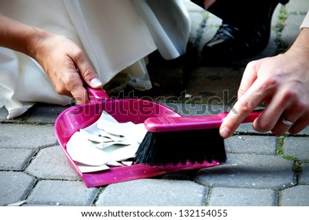 Bride and bridegroom sweeping cullet. - stock photo
