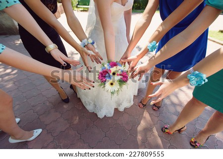 bride and bridesmaids admiring wedding bouquet - stock photo