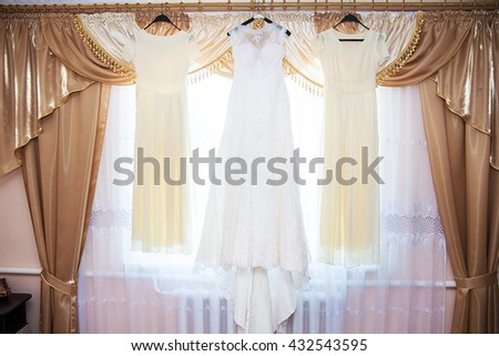 bride and bridesmaids dresses hanging on hangers