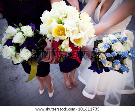 Bride and bridesmaids holding their bouquets - stock photo