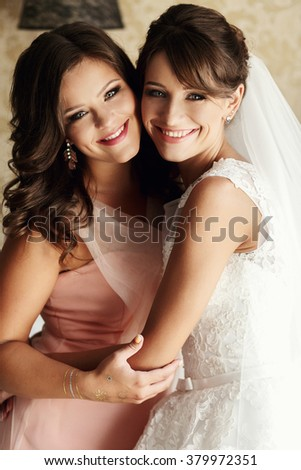 Bride and bridesmaids on the wedding day in hotel room - stock photo