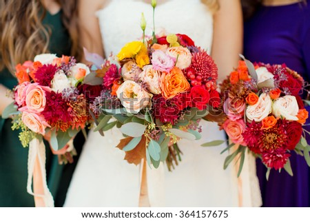 Bride and bridesmaids with autumn bouquets