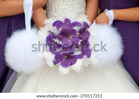 bride and bridesmaids with purple orchid bouquet - stock photo