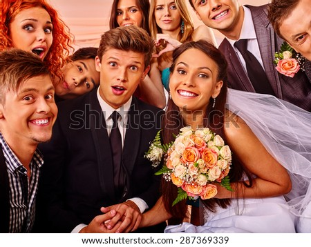 Bride and groom and guests in photobooth. Wedding. - stock photo