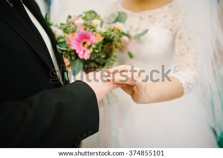 bride and groom are changing rings on their wedding