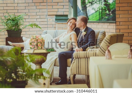Bride and groom are sitting at the table in the cafe