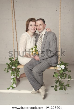 bride and groom are swinging in the Studio
