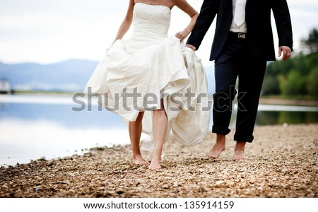 Bride and groom are walking outside together - stock photo