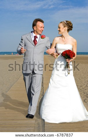 Bride and Groom arm in arm walking on beach holding glasses of bubbly and bridal bouquet of red roses