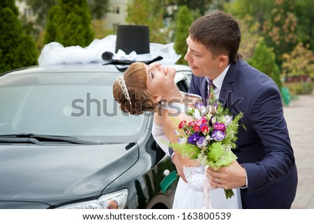 bride and groom around a decorated car - stock photo