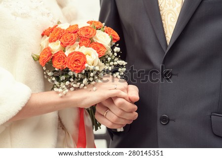 bride and groom at a registry office. bride is holding a wedding bouquet. selective focus - stock photo
