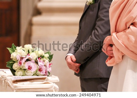 bride and groom at the altar with bouquet of flowers - stock photo