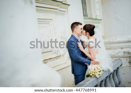 Bride and groom at wedding Day walking Outdoors near architecture. Bridal couple, Newlywed woman and man embracing with love