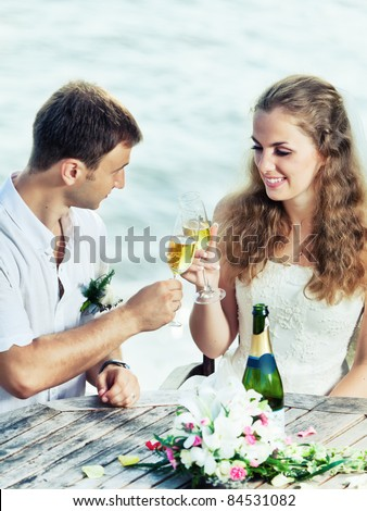 Bride and groom at wedding table near the sea - stock photo