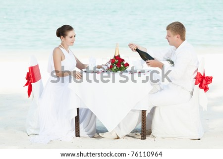 Bride and groom at wedding table on the beach - stock photo