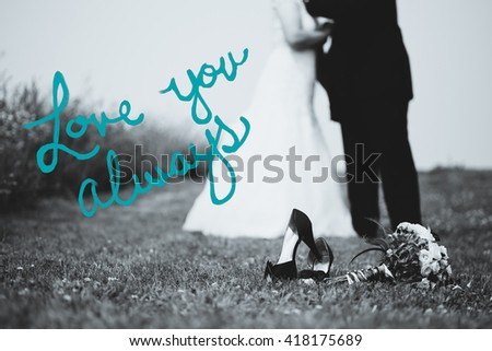 """Bride and groom blurred in background. Shoes and flowers in focus with copy space on left. In black and white with teal text that reads """"Love you always"""". - stock photo"""