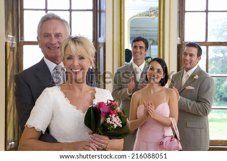 Bride and groom by bridesmaid and ushers clapping, smiling, portrait - stock photo