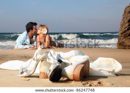 Bride and groom by the sea on their wedding day - stock photo