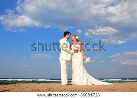 Bride and groom by the sea on their wedding day in Greece - stock photo