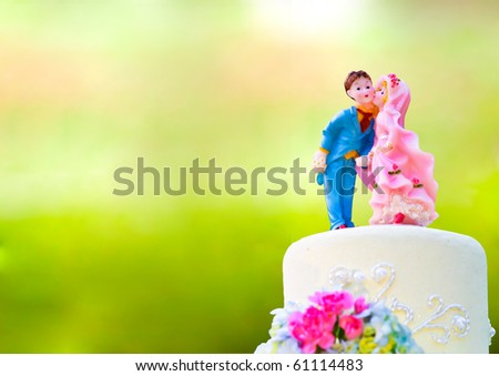 Bride and Groom cake toppers on a wedding cake - stock photo