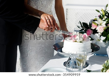 Bride and groom carving delicious white wedding cake closeup - stock photo
