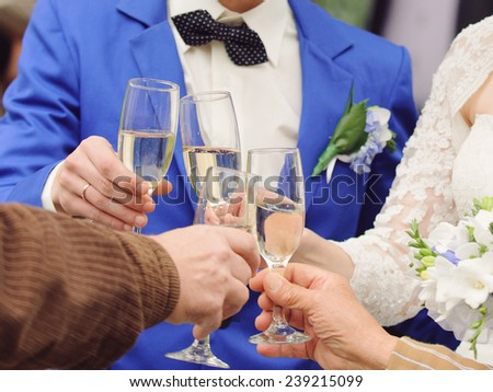 bride and groom clanging glasses with guests - stock photo