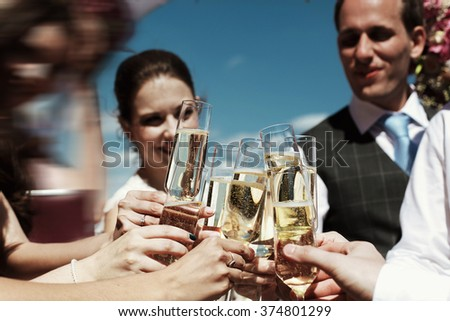 Bride and groom clinking glasses of champagne or white wine