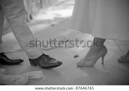 Bride and groom couple dancing showed legs/shoes black and white. - stock photo