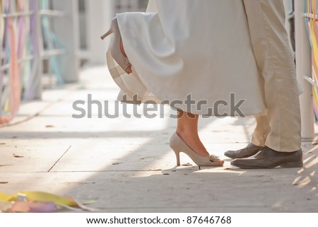 Bride and groom couple stand hugging showed legs/shoes - stock photo