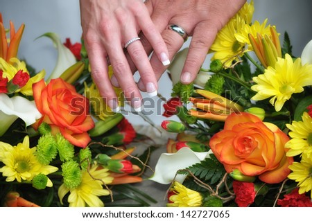 bride and groom crossing hands to show wedding rings over her bouquet