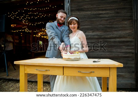 Bride and groom cut the cake and feed each other on their wedding day at the reception. - stock photo