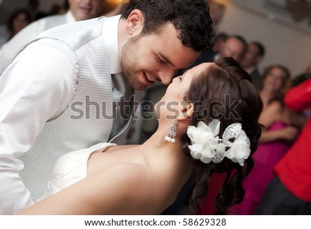 Bride and groom dancing in front of their friends - stock photo