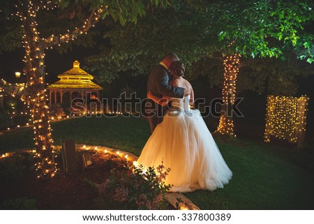 bride and groom dancing in garden with a gazebo at night - stock photo