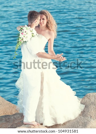 Bride and groom dancing on a rock.