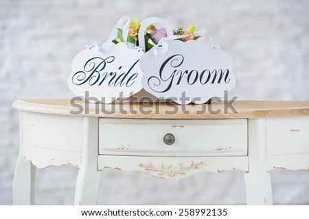 Bride and groom decoration boards with flowers on vintage table  - stock photo