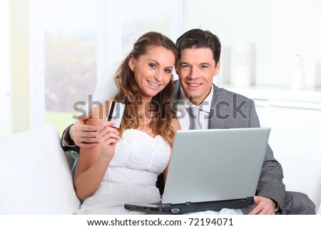 Bride and groom doing shopping on internet at home - stock photo