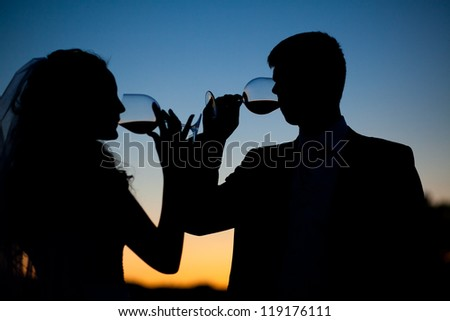 Bride and groom drink wine at sunset - stock photo
