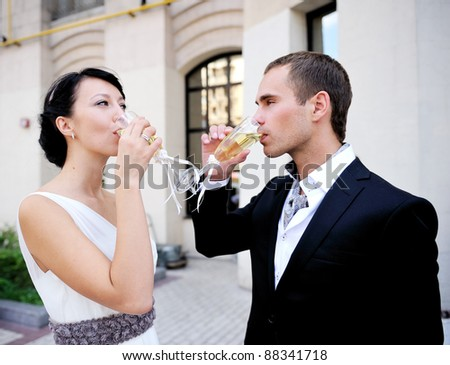 Bride and groom drinking champagne outdoor after a wedding ceremony - stock photo