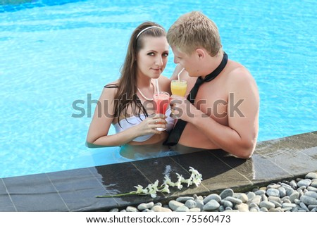 Bride and groom drinking juice in swimming pool
