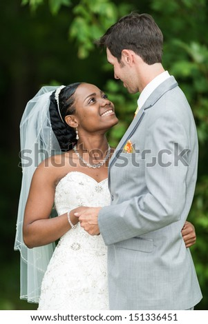 Bride and groom embrace and looking at each other - stock photo