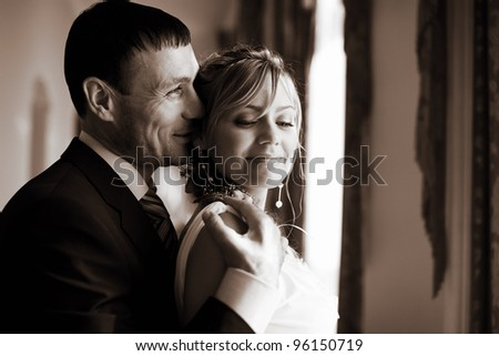 Bride and groom embraces in the hall in front of window - stock photo